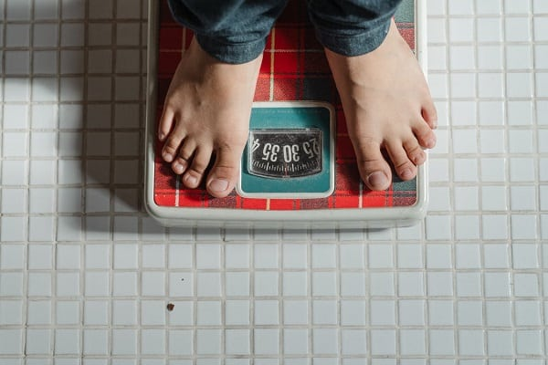 woman standing on old style scales