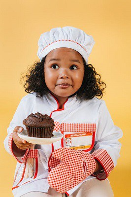 A little girl holding a chocolate muffin looking confused or pensive