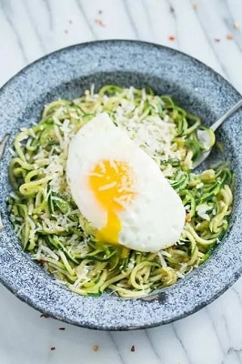 zucchini noodles aglio and olio in a bowl with a fork and egg on top