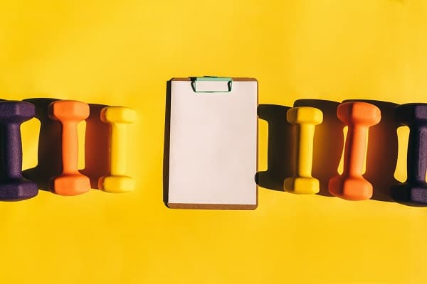Clipboard and hand weights on yellow background
