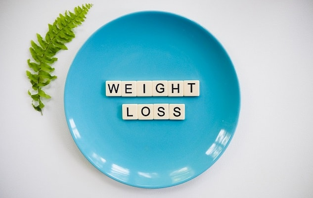 Blue plate with weight loss spelled in scrabble letters