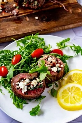 stuffed flank steaks with bacon and feta on a plate with lemon slices