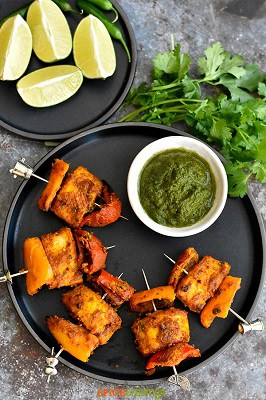 Keto tandoori fish from air fryer on a plate with garnishes