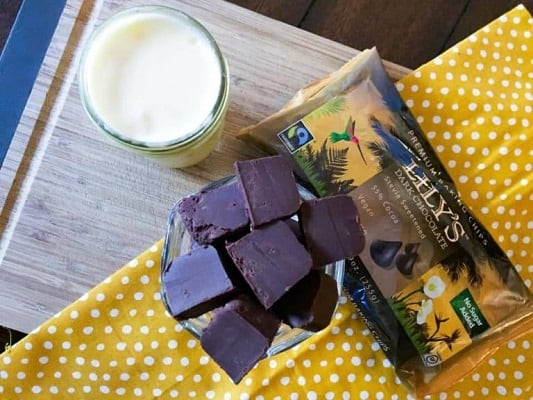 Keto chcolate fudge with a glass of milk on a table