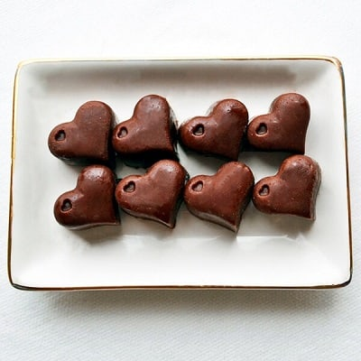 8 Keto chocolate peanut butter fat bombs in the shape of hearts on a plate