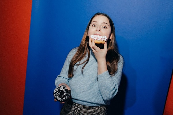 Woman guiltily eating junk food in front of blue wall