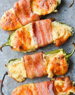 Bacon wrapped keto stuffed jalapeno poppers on a hot plate