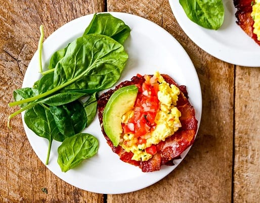 Breakfast tacos in bacon shell on a plate with lettuce