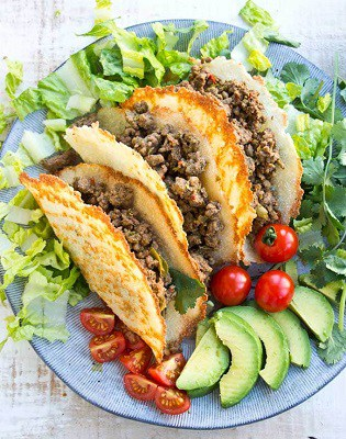 Cheesy shell keto tacos with beef filling on a plate with vegetables