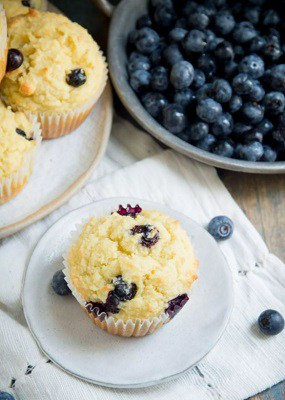 tender low carb blueberry muffin on a plate next to bowl of blueberries